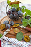 Plums in a mesh basket Royalty Free Stock Images