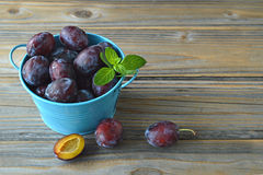 Plums and mint in the bowl. On wooden background Royalty Free Stock Photo