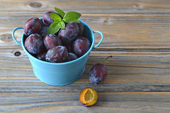 Plums and mint leaves in the bowl Royalty Free Stock Image