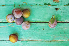 Plums on old turquose color surface. Plums on old turquose color wooden weathered surface Royalty Free Stock Image