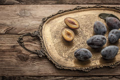 Plums on the old vintage brass tray  with film filter effect Royalty Free Stock Photo