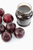Plums beside open jar of plum jam on white background,close up Stock Photos