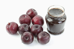 Plums beside open jar of plum jam on white background Royalty Free Stock Images