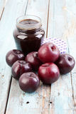 Plums beside open jar of plum jam on wooden table Royalty Free Stock Images