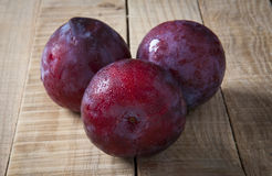 Plums over rustic wooden table Stock Photo