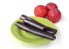 From plums pastilles lie on the green plate and fresh plums Stock Photos