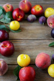 Plums and peaches on wooden boards Stock Photo