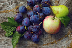 Plums, pear and apple on a wooden background. Stock Image