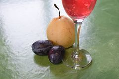 Plums pear and wineglass Stock Photos