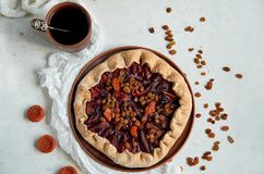 Plums pie with dried apricots on dark plate decorated with brown raisins and a cup of tea on light table with white cloth Stock Photo