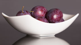 Plums on plate  on grey background. Royalty Free Stock Photo