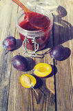 Plums and plum jam in a glass jar and a wooden spoon Stock Photography