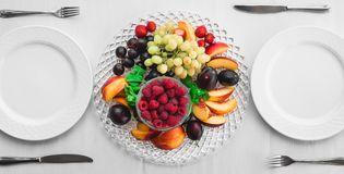 Plums raspberry peach strawberry grapes. Dessert in a restaurant served for two persons Royalty Free Stock Images