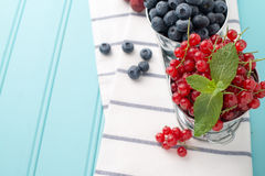 Plums, red currants and blueberries in small metal bucket Royalty Free Stock Photography