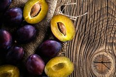 Plums ripe fresh on the wood texture background. royalty free stock photo