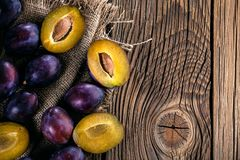 Plums ripe fresh on the wood texture background. royalty free stock images