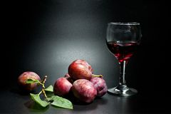 Plums ripe and juicy shot close-up on a dark background and a glass of wine stock photography