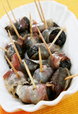 Plums rolled in prosciutto Stock Image