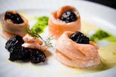 Plums rolled up in salmon fish Stock Images