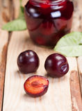 Plums on rough wooden table. In background glass jar with jam. stock photos