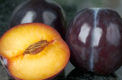 Plums, with sliced half-plum Royalty Free Stock Photography