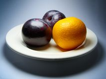 Plums and tangerine on plate. Royalty Free Stock Images
