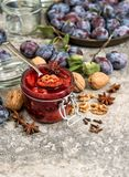 Plums walnuts marmalade spices in jar Fruit jam. Plums walnuts marmalade with spices in jar. Fruit jam on stone background Stock Photography