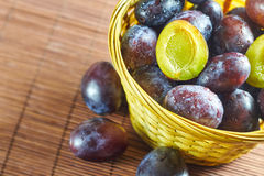 Plums in weaved basket Royalty Free Stock Images