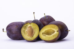 Plums on white background with halved one Stock Image