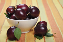 Plums in white bowl. Fresh ripe plums in white bowl. Selective focus, shallow dof Stock Photos