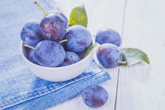 Plums on the white wooden table Royalty Free Stock Photo