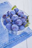 Plums on the white wooden table Royalty Free Stock Photos