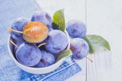 Plums on the white wooden table Stock Photos