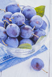 Plums on the white wooden table Stock Images