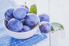 Plums on the white wooden table Stock Image
