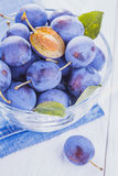 Plums on the white wooden table Royalty Free Stock Images
