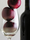 Plums and Wine. Plums inside a cup and a bottle of wine stock images