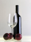 Plums and Wine. Plums, a glass and a bottle of wine Royalty Free Stock Image