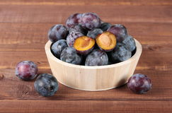 Plums in  wooden bowl Stock Photos