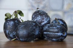 Plums on wooden table indoor. Picture of fresh plums on wooden table indoor Royalty Free Stock Photo