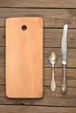 Plundrat bräde, gammal sked och kniv Arkivfoto