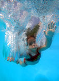 Plunge. Little girl diving in pool royalty free stock photography