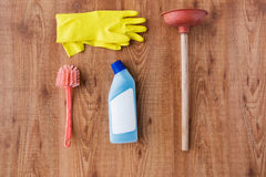 Plunger with cleaning stuff on wooden background Royalty Free Stock Photography