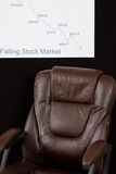 Plunging stock market. Broker empty chair with a falling stock market chart Royalty Free Stock Images