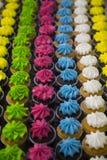 Plus de trois douzaine petits gâteaux brillamment colorés dans des rangées verticales Photos stock