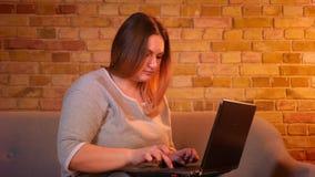 Plus format sitter modellen med långt hår på soffan som uppmärksamt skriver på bärbara datorn i hemtrevlig hem- atmosfär stock video