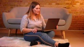 Plus format sitter modellen på golvet som talar i videochat på bärbara datorn som den är fundersam och glad i hemtrevlig hem- atm stock video
