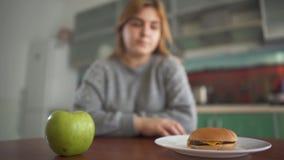 Plus format tänker flickan som sitter på en suddig bakgrund att hon bör äta en smaklig hamburgare eller ett saftigt grönt äpple lager videofilmer