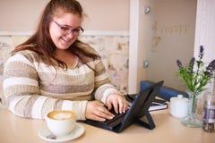 Plus formatkvinnan som ler, medan arbeta i ett ljust kafé arkivbild