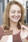 Plus formatkvinnan som tycker om äta stången av choklad Arkivbild